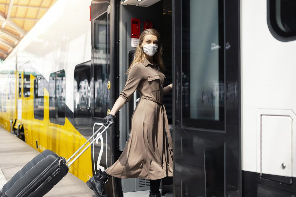 businesswoman wearing a mask boards a train