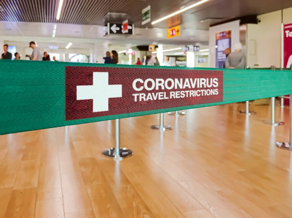 Green ribbon barrier inside an airport with the warning of travel restrictions due to the spread of the dangerous Coronavirus