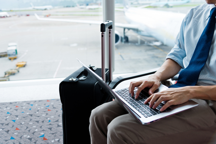 businessman working on laptop in airport