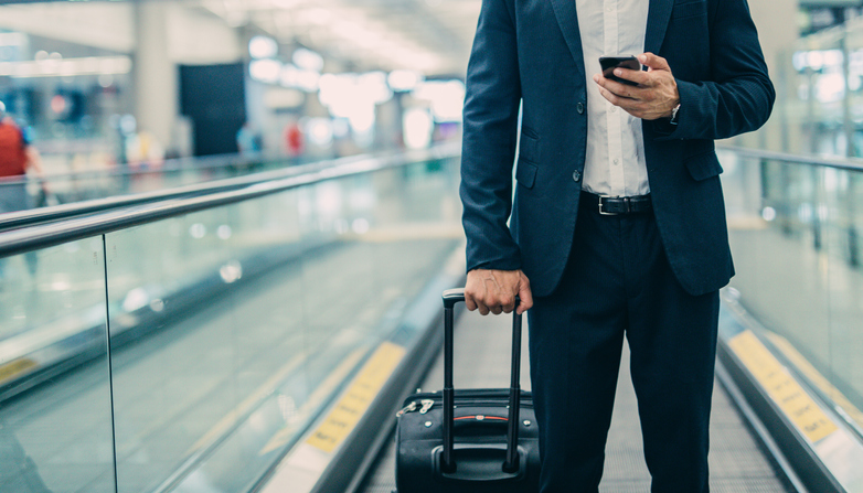 businessman walking through airport with luggage and cell phone