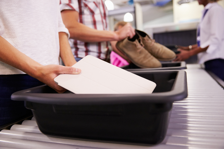 people placing items into trays for airport security check