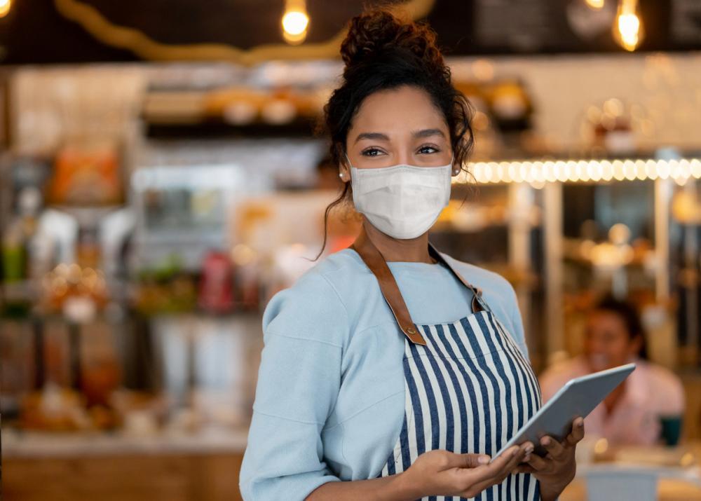 waitress working at a restaurant wearing a facemask