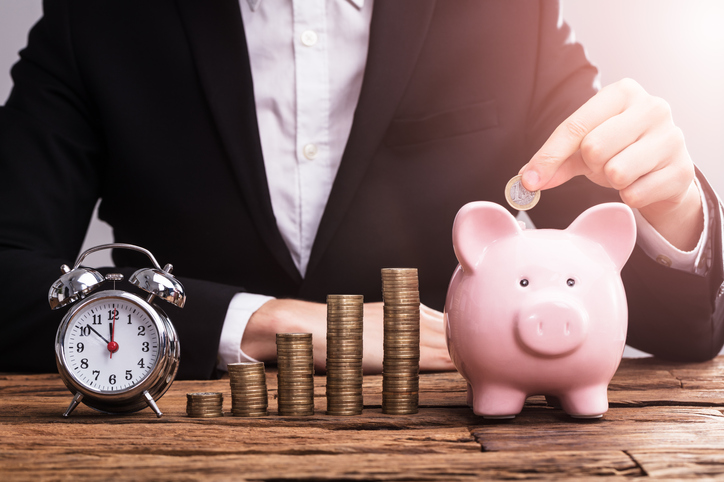 business person places coins into piggy bank next to clock
