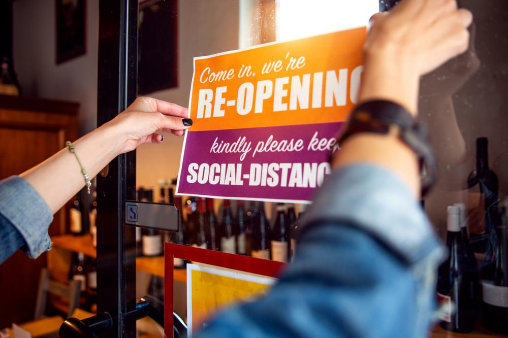 employee placing reopening sign on business door