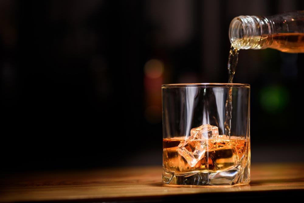 liquor being poured into a rocks glass