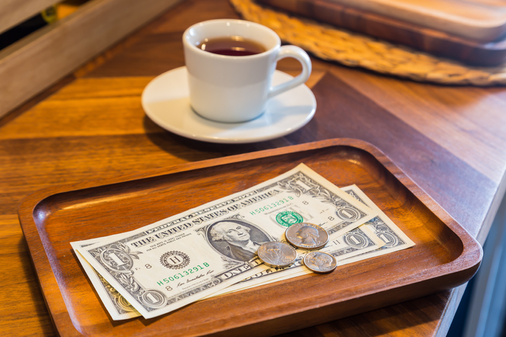 dollar banknotes and coins next to coffee cup