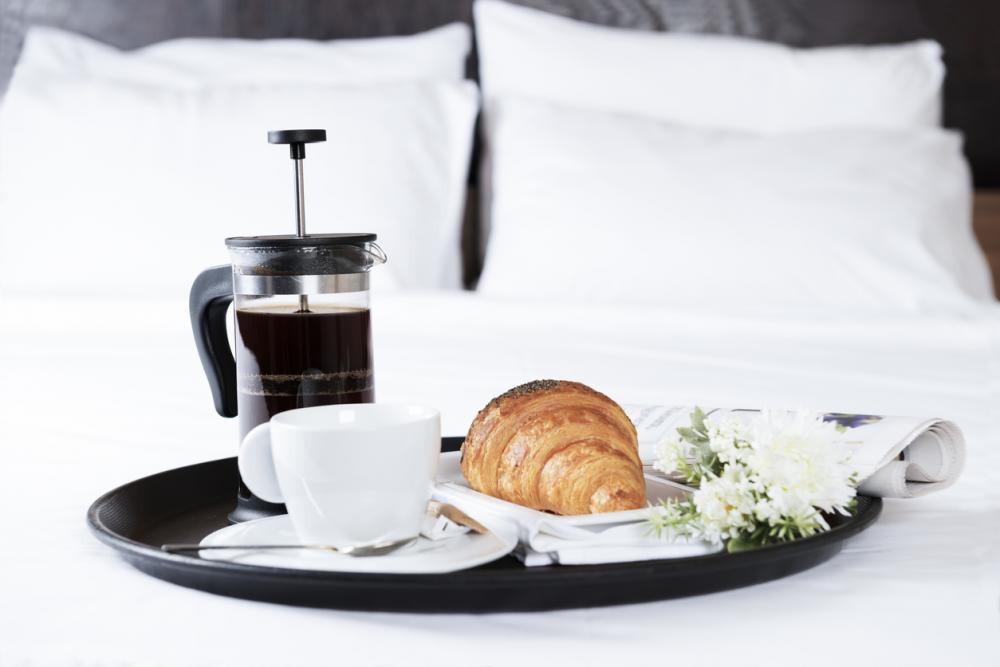 Breakfast with croissant, french press coffee, flowers and newspaper on bed with white sheets