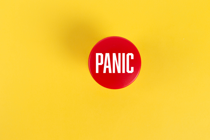 red panic button against solid yellow background