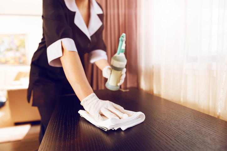 housekeeper wipes down table