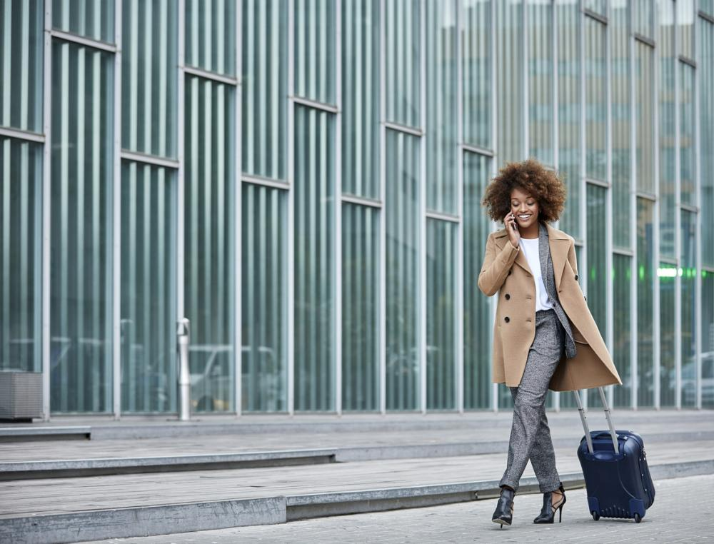businesswoman with luggage talks on smartphone