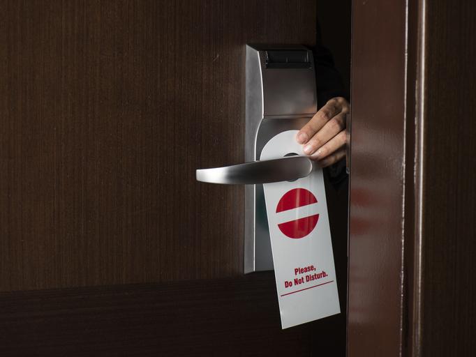 placing Do Not Disturb sign on room door