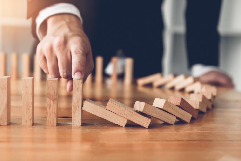 businessman stops blocks from falling