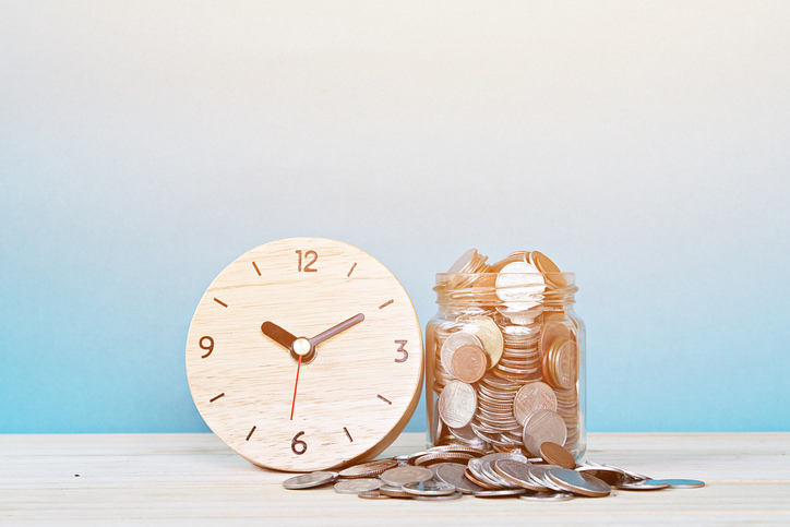 wooden clock next to jar overflowing with coins
