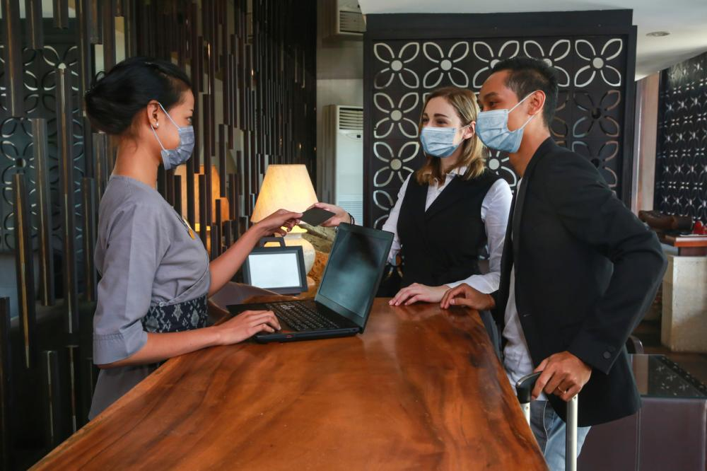 concierge and customers wearing masks while completing check-in to hotel