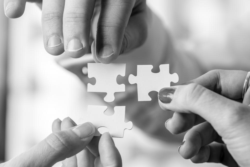 three people connecting three puzzle pieces