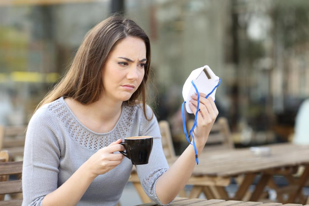 a customer looks at a face mask with displeasure as she sits in an outdoor restaurant drinking coffee