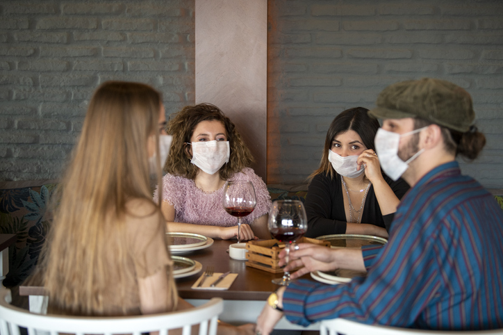 group of friends wearing masks in a restaurant