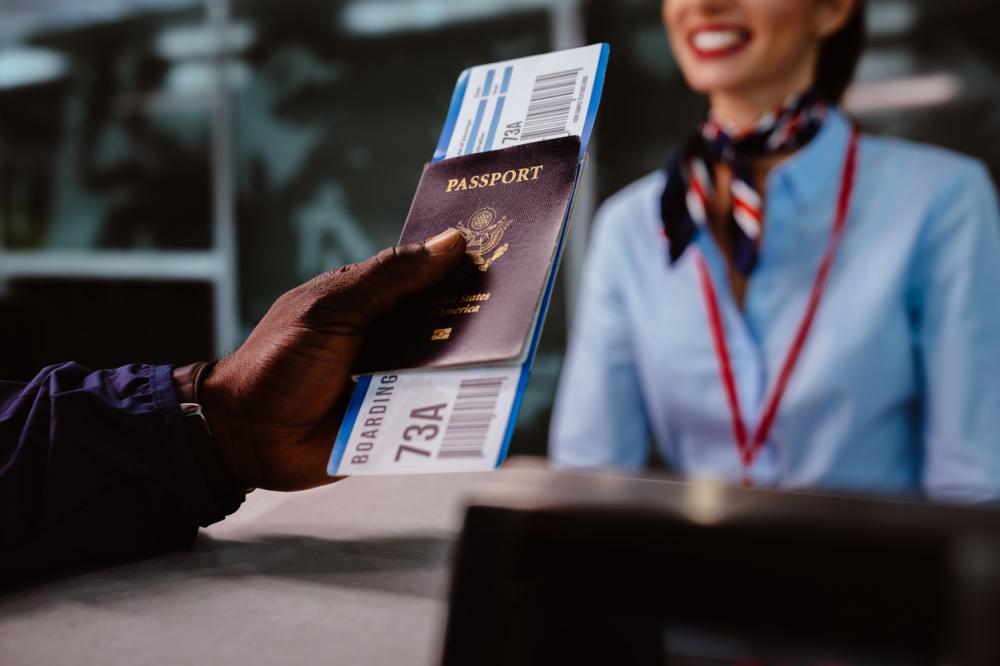 person handing passport and flight ticket to gate agent