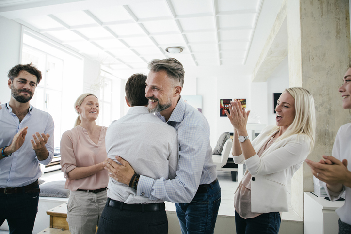 celebrations in office; two employees hug