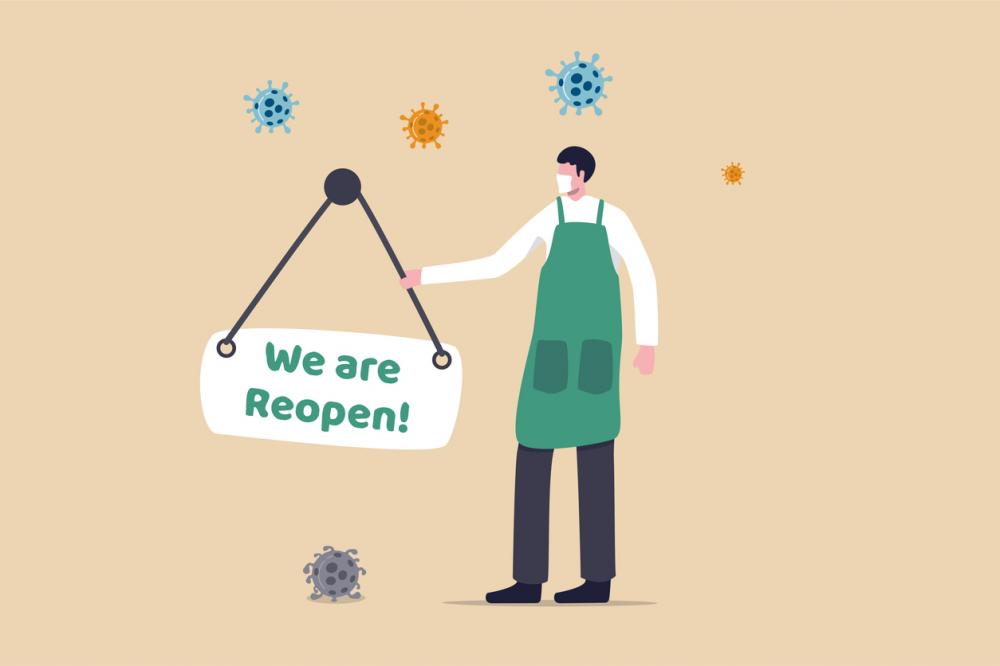 """employee with """"we are reopen"""" sign"""
